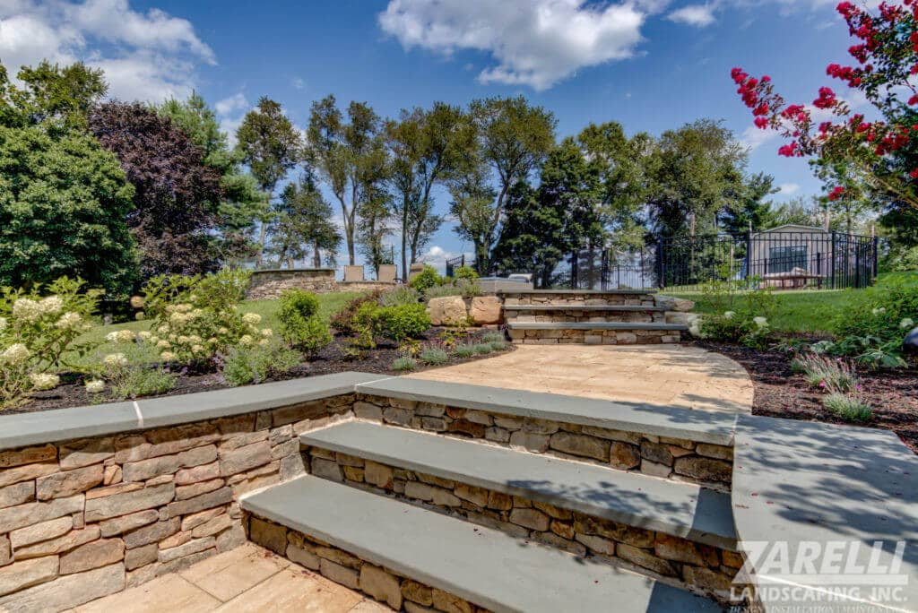 outdoor space with retaining wall and paver walkway and steps